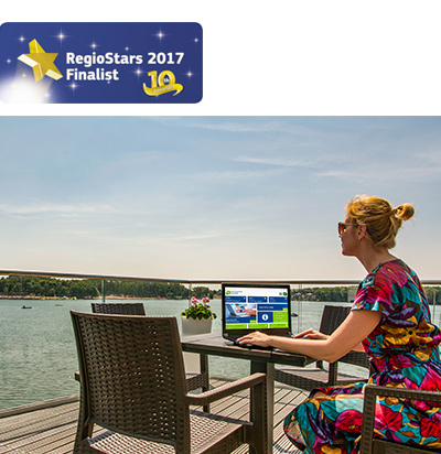 A woman uses the e-payment system on her laptop while relaxing beside a lake ©Integrated Public Services Platform Implementation and Electronic Payments of Olsztyn
