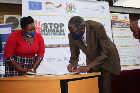 Uganda State Minister for Internal Affairs, M. Kania Mario Obiga, signs the National Action Plan for Prevention of Trafficking in Persons,